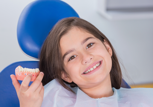 Portrait of a smiling young patient showing model in dental clinic