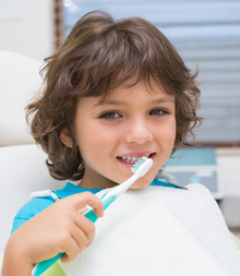 Little boy in dentists chair using toothrbrush at the dental clinic